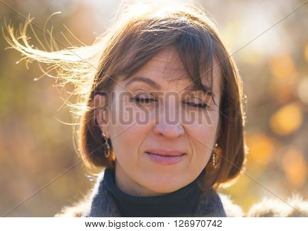 Portrait of a woman covering the eyes on a sunny day in the park  age of 40 years