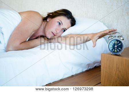 tired woman llying in bed reaching out to turn off her alarm