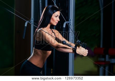 young fitness woman execute exercise with exercise-machine Cable Crossover in gym, horizontal photo.