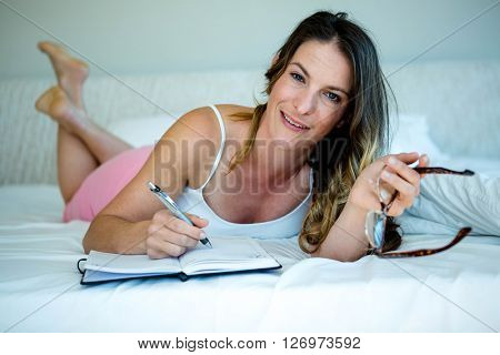 smiling woman with glasses, lying on a bed writing in a book