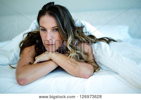 angry looking woman lying in bed with her head in her hands