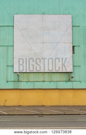 Old obsolete square shaped blank billboard surface as copy space mounted on wall