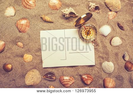 Blank postcard in hot beach sand and magnetic compass with some sea shells copy space for summer holiday vacation message top view retro toned.