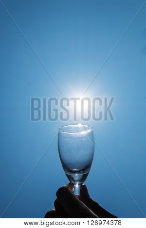 Wine glass on blue sky with sun lens flare effects