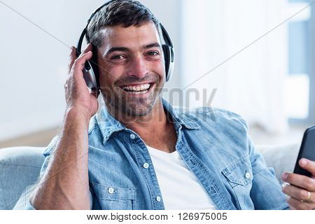 Young man listening to music while using mobile phone in living room