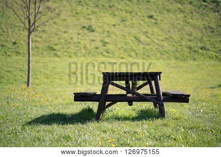 Wooden table and bench on a green meadow