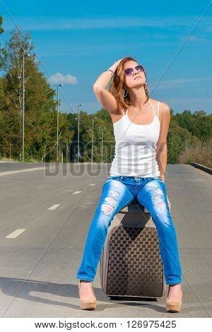 Young Girl Traveling Across The Country With A Suitcase Hitchhiked