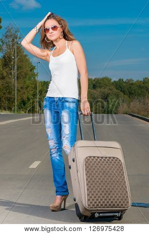 Vertical Portrait Of A Traveler On The Road With A Suitcase