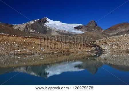 Glacial landscape reflecting in calm lake, British Columbia