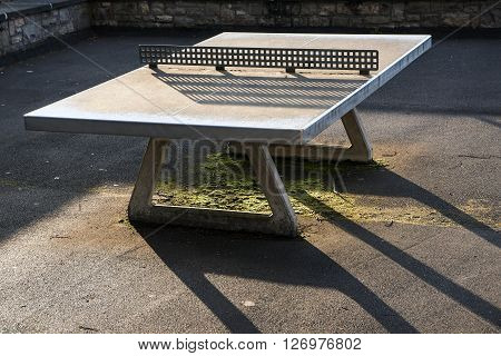 stable outdoor ping pong table from concrete with a net of metal in the back light