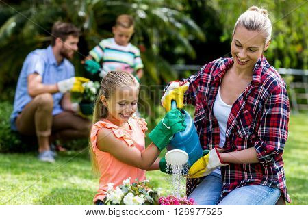 Happy mother and daughter watering flowers in yard