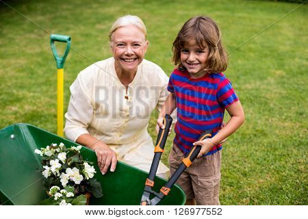 Portrait of boy with granny holding scissors over wheelbarrow at yard
