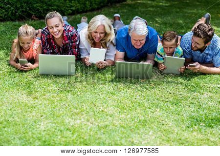 High angle view of happy family with technologies lying in yard