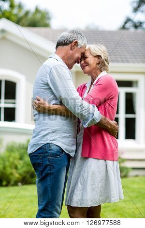 Happy senior couple standing with arms around outside house in yard