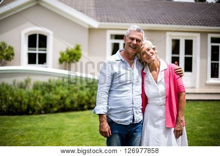 Smiling senior couple with arms around standing outside house in yard