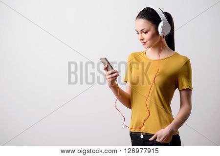 Have some rest. Cheerful pleasant attractive girl holding her hand in a pocket and listening to music while standing isolated on grey background ** Note: Soft Focus at 100%, best at smaller sizes