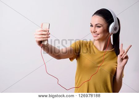 Say cheese.  Delighted positive smiling girl making selfies and listening to music while standing isolated on grey background