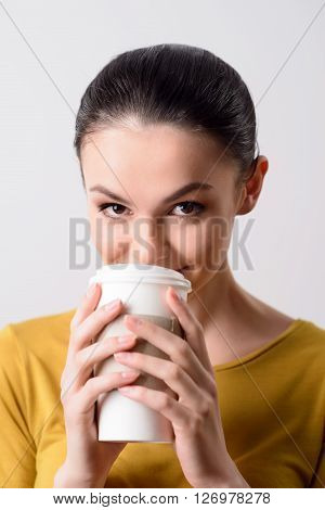 In a high spirit. Cheerful beautiful delighted girl drinking coffee and looking at you while standing isolated on grey background