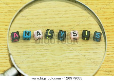 Magnifying glass emphasize on word ANALYSIS arranged from plastic alphabet block. Concept of economy, financial, study, research.