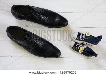 father's day kids sneakers with a bouquet of daisies and daddy's black men shoes on a white painted wooden floor view from above