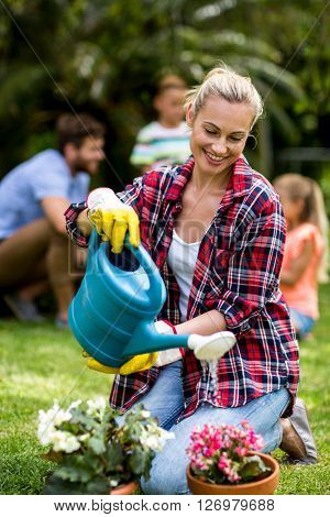 Happy woman watering flowers on grass at yard