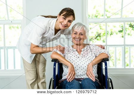 Portrait of smiling senior woman with nurse at health club