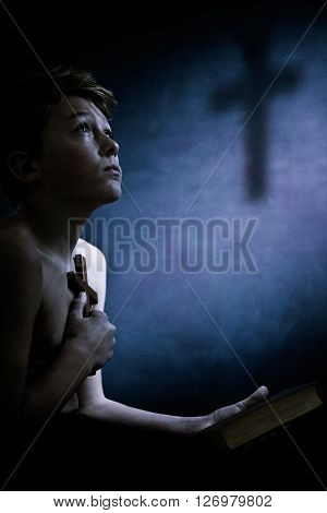 Religious Young Boy Clasping A Cross