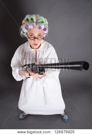Top view of grandmother posing with rifle and looking at camera. Beautiful lady looking as hunter in studio.