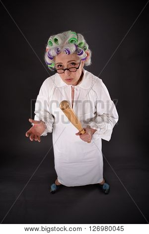 Top view of crazy furious grandmother looking at camera while holding criket bat in studio. Studio shot of excited and astonished senior lady.