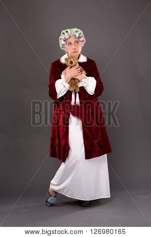 Beautiful grandmother holding teddy bear over grey background. Elderly lady thinking about old times in studio.