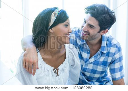 Happy young couple embracing each other at home