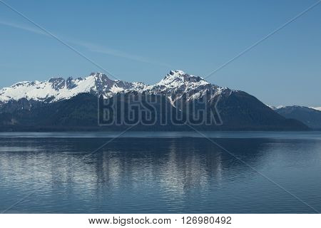 Snowcapped mountains reflect in Alaska's Glacier Bay