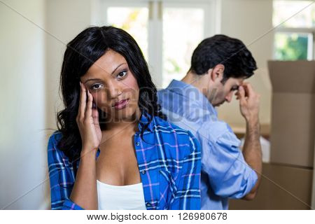 Young couple standing back to back and ignoring each other at home