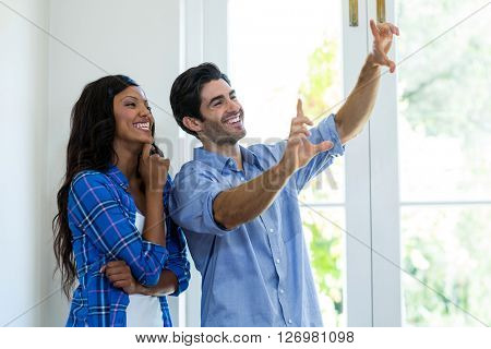 Couple framing a picture with hands at home
