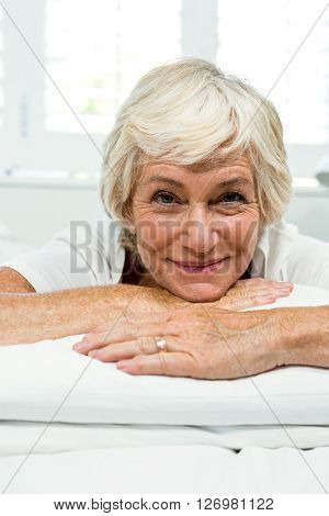 Portrait of smiling senior woman relaxing on bed at home