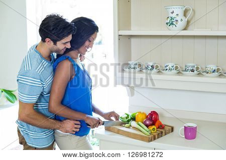 Man embracing woman while chopping vegetables in kitchen at home
