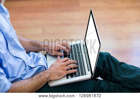 Mid-section of man sitting on floor and using laptop at home
