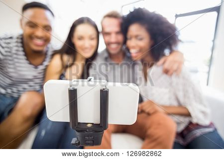 Friends sitting on sofa and posing for a selfie in living room
