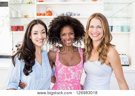 Portrait of beautiful women standing with arm around in kitchen at home
