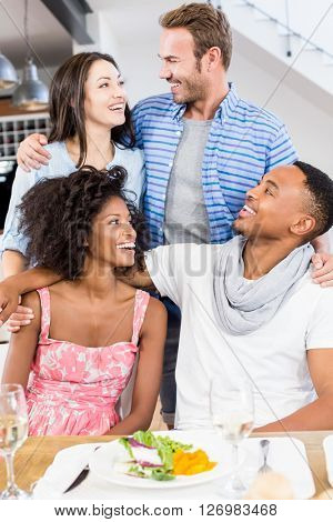 Friends looking at each other and smiling in dining room