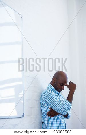 Upset man with eyes closed and finger on the forehead leaning against a wall in office