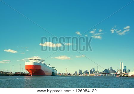 Large cargo ship in Yarra river with Melbourne CBD skyline in the background.