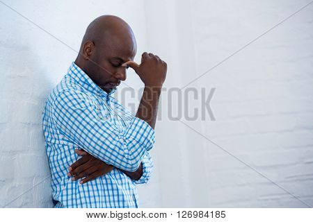 Upset man with eyes closed leaning against a wall in office