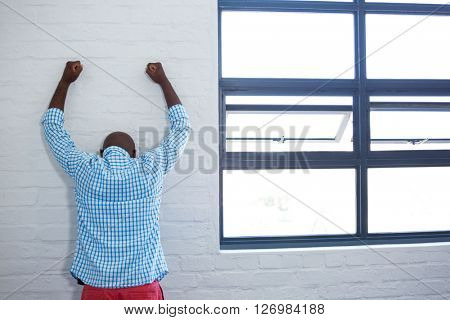 Rea view of upset man leaning against wall in office