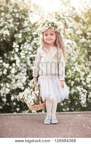 Smiling baby girl 3-4 year old holding basket with flowers outdoors. Looking at camera. Wearing stylish skirt and sweatshirt.