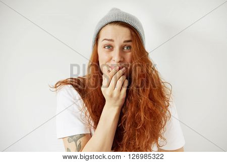 Close Up Isolated Portrait Of Young Redhead Woman Laughing, Covering Mouth With Her Hand With Surpri