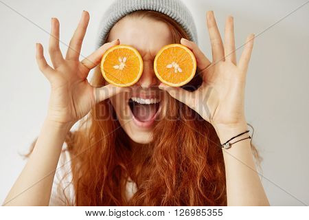 Close Up Isolated Portrait Of Young Redhead Woman Holding Halved Oranges At Her Eyes. Headshot Of Fu