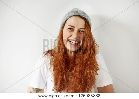 Close Up Studio View Of Cheerful Young Woman With Healthy Freckled Skin And Blue Eyes Happily Smilin