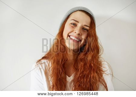 Cute Happy Young Woman In Gray Cap And White T-shirt Looking And Smiling At The Camera. Isolated Por