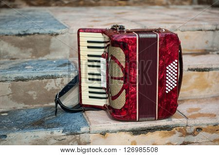 Musical instrument red accordion on a vintage background